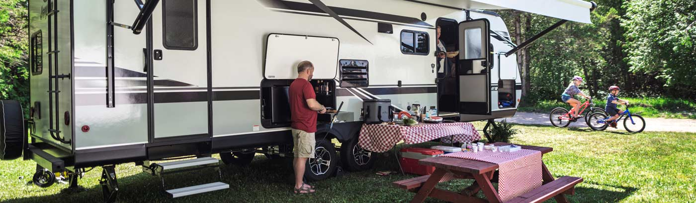 Family outside their Jayco Jay Feather travel trailer, with father cooking and kids riding bikes.