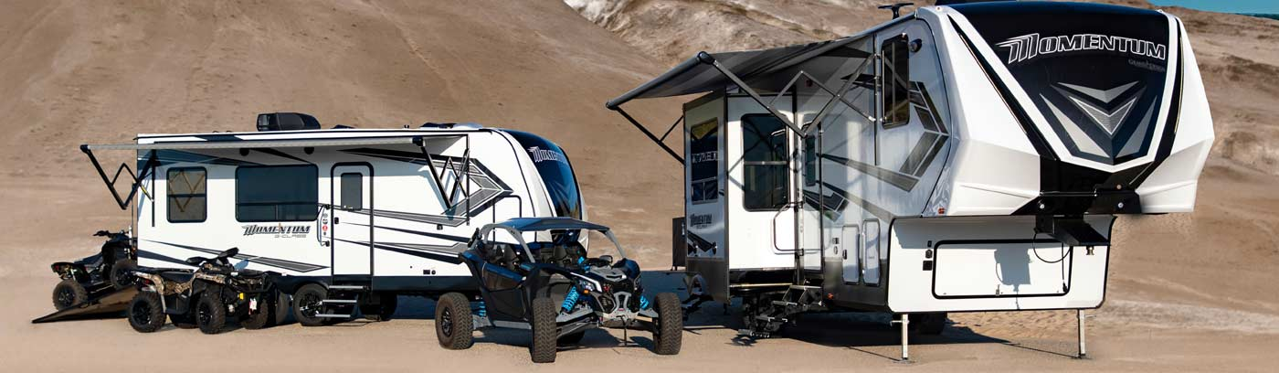 Photo of two Grand Design toy haulers in desert with ATVs.