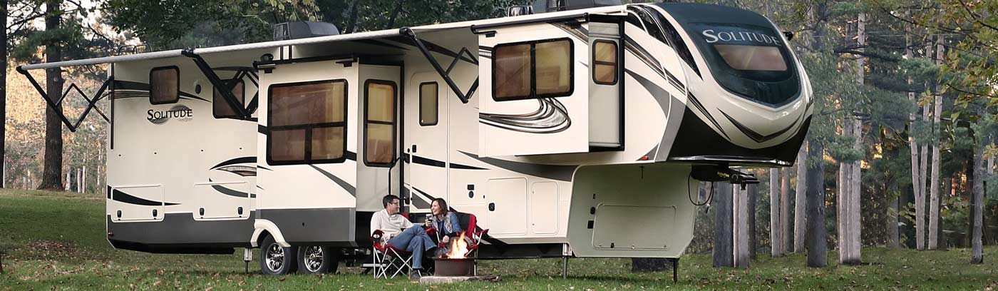 Photo of couple camping in their Grand Design Solitude fifth wheel.
