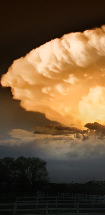 Large violent storm cloud over farm.