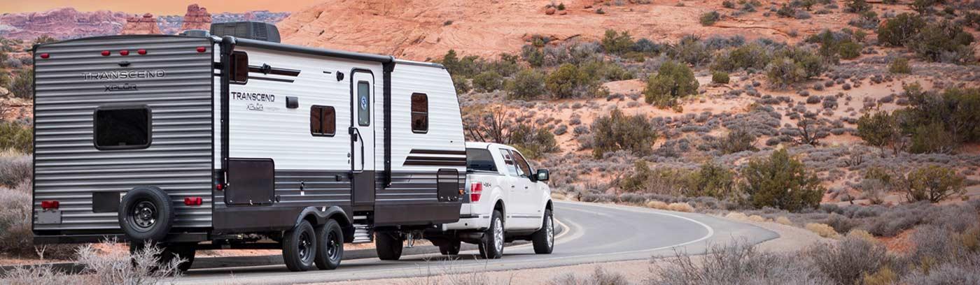 Grand Design Transcend Transcend XPLOR being pulled by pickup on desert highway.